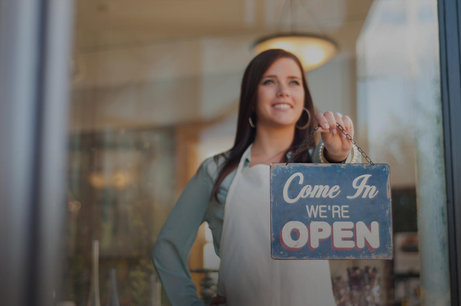 Page background image - shopkeeper with sign that reads come in, we're open