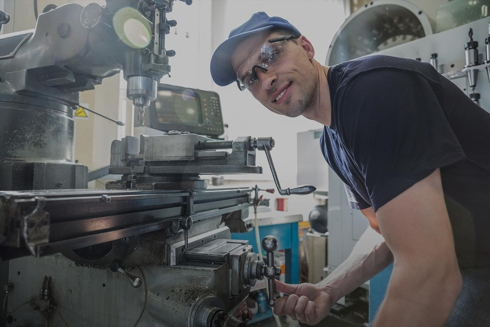 Page background image - industrial machinist smiling beside his machine