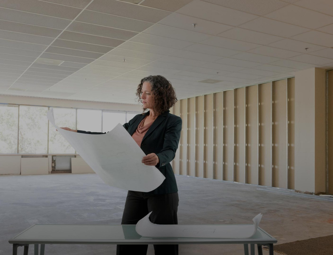 Page background image - Woman in empty office looking at office blueprints