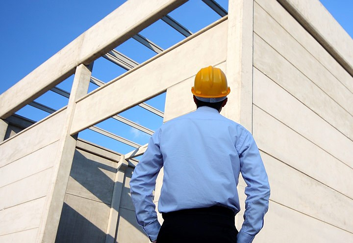 Businessman in hard hat peering up at building or warehouse under construction