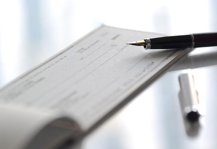 Image of a checkbook and pen on a desktop