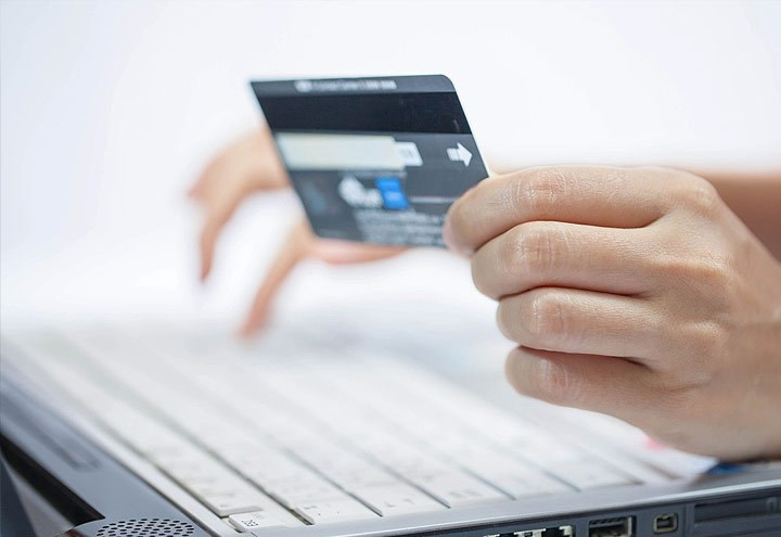 Image of holding a purchasing card in one hand and typing with another