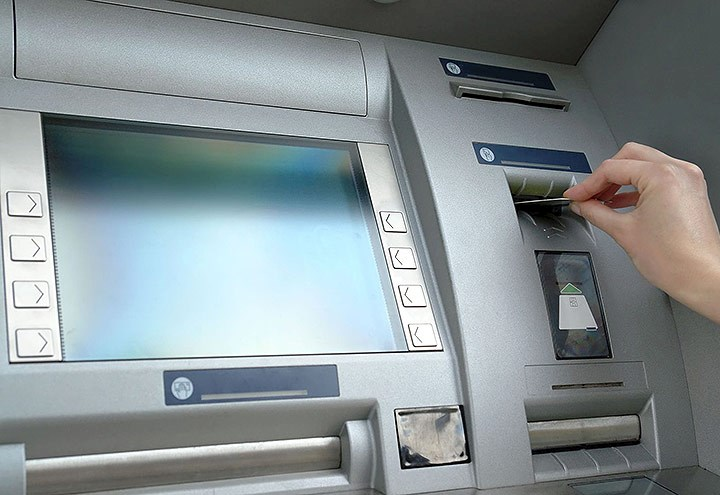 Image of a hand inserting a card into an ATM machine
