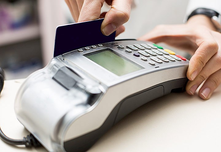 Image of credit card being swiped through a merchant POS terminal