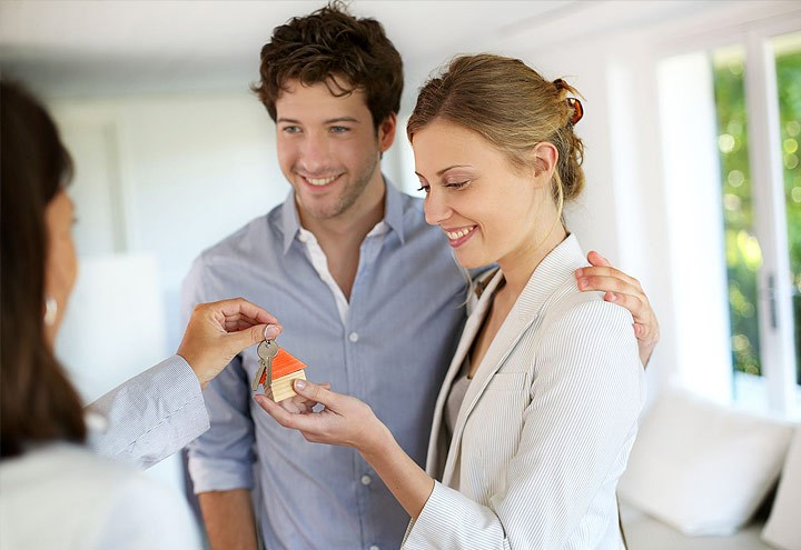 Photo of a woman handing house keys to a smiling couple