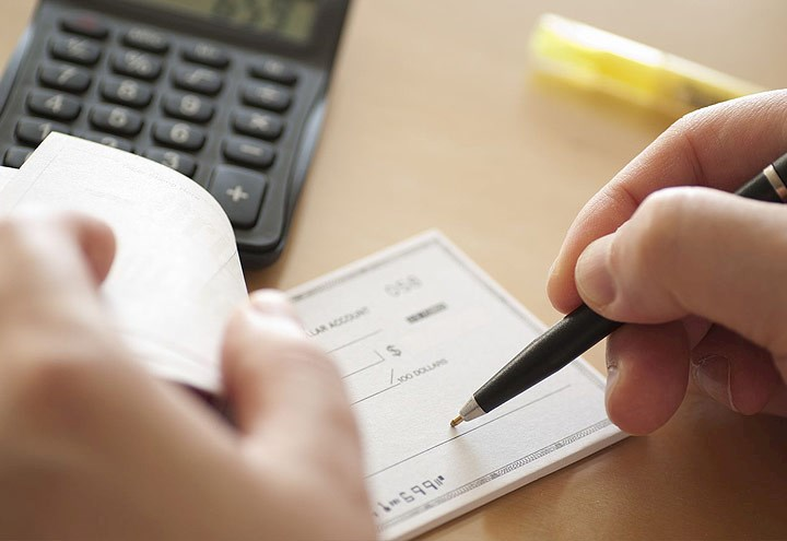 Image of person writing a check