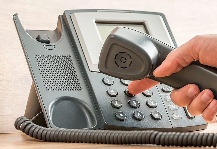 Image of person dialing a phone